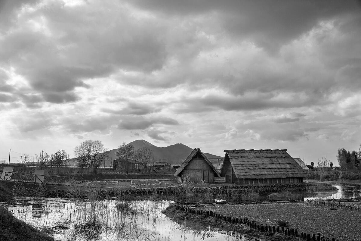 Insediamento con scorcio sul Vesuvio del parco archeo-fluviale di Longola. Foto di Sossio Mormile