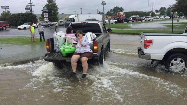 Residents flee flooded Baton Rouge as waters continue to rise on Saturday, August 13, 2016. (Phin Percy)
