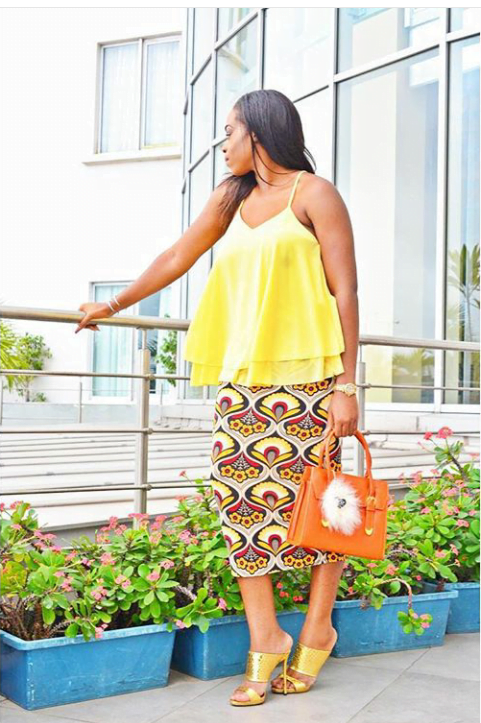 layred tank top and a print midi skirt with orange bag