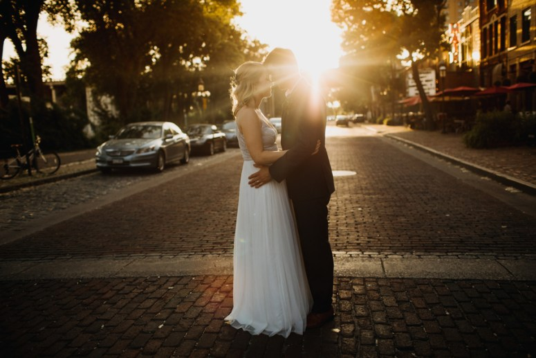 bride and groom pose on cobblestone street