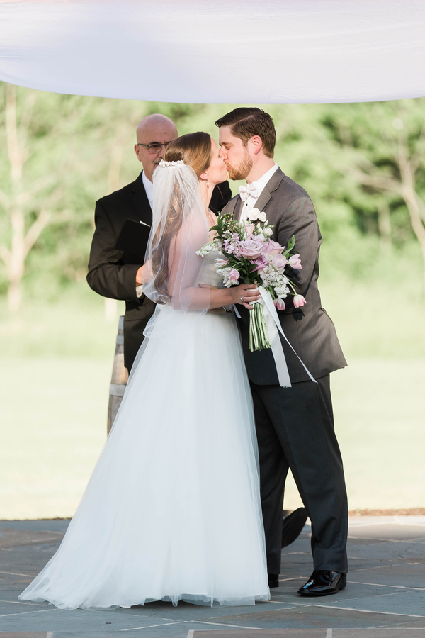 bride and groom first kiss after wedding ceremony