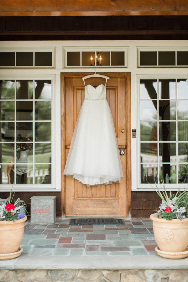 wedding dress on hanger before ceremony at barn