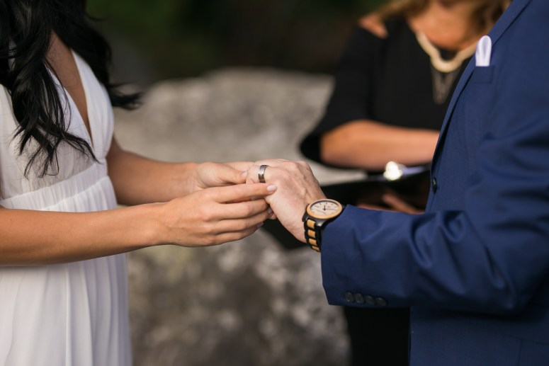 bride placing ring on grooms finger
