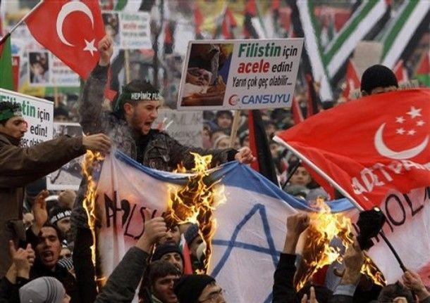 Protestujący palą prowizoryczną flagę Izraela podczas demonstracji solidarności z Gazańczykami