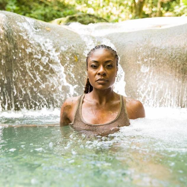 Jully Black standing in water with beautiful waterfalls