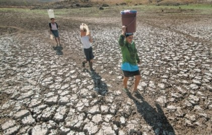 Women carrying water across a dry lakebed