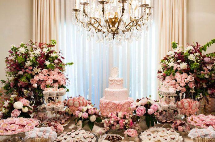 Decoração muito chique para chá bebê, com mesa cercada de rosa e folhagens brancas e roxas, bolo e doces clássicos, lustre no teto, e cortina ao fundo.