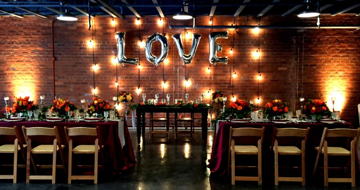 String Lighting and LOVE balloons as backdrop for wedding head table