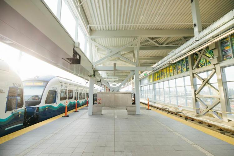 A Link train can be seen on the left side of the platform at Northgate Station, with stained glass art on the right.