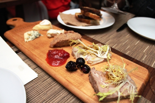 A mixtuer of meats and cheeses on the charcuterie platter.