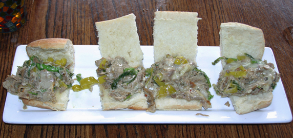 The Porchetta 'Louie': Porchetta, rapini, and sliced peperoncini peppers with melted provel cheese.