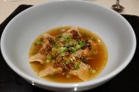 Steamed dumplings in a dipping sauce