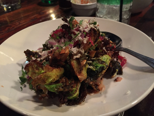 Brussel sprouts blistered and seared in chipotle aioli, pickled onion and herbs