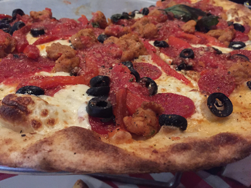 Pizza with spicy chicken sausage, pepperoni, olives and roasted red pepper.