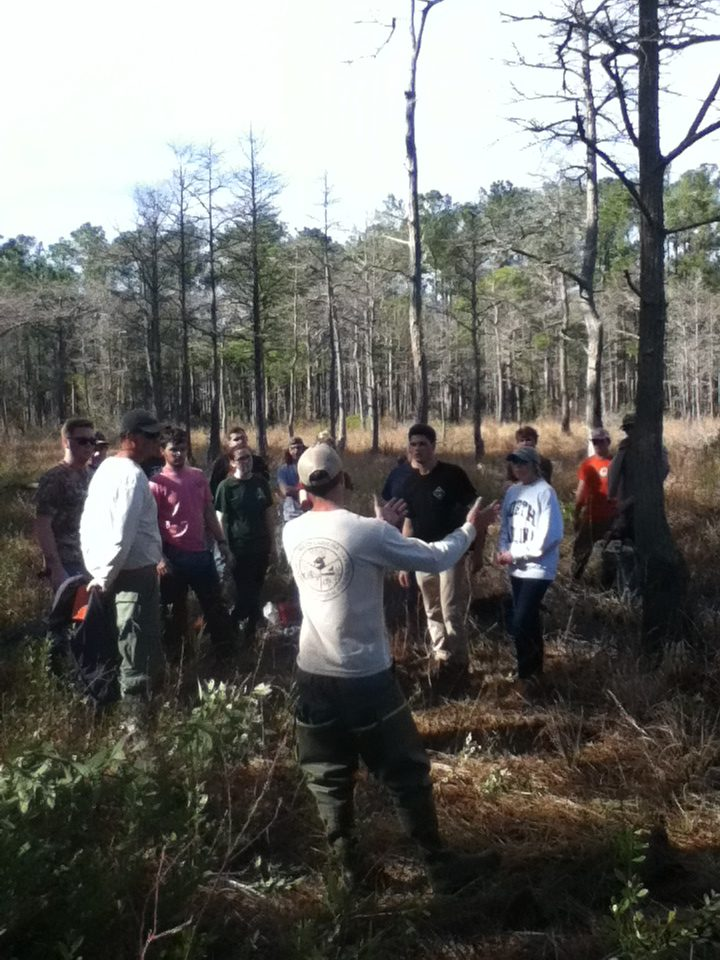 An SCDNR employee standing in front of a group of students outdoors while motioning with his hands mid-explanation.