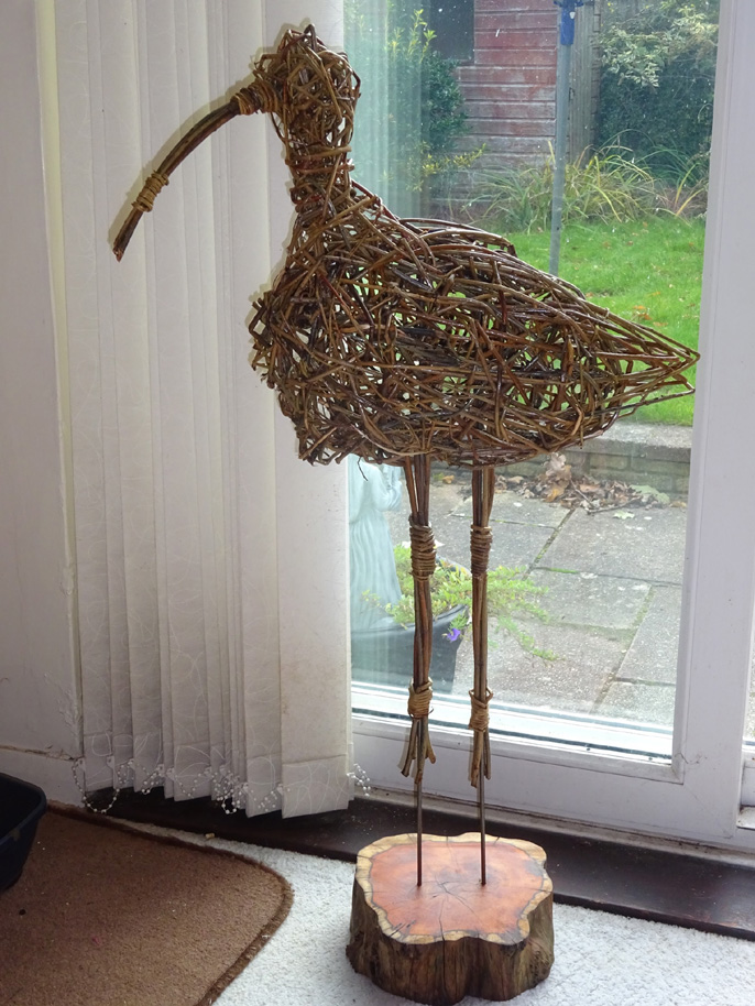 willow stag head sculpture made by students against white wall