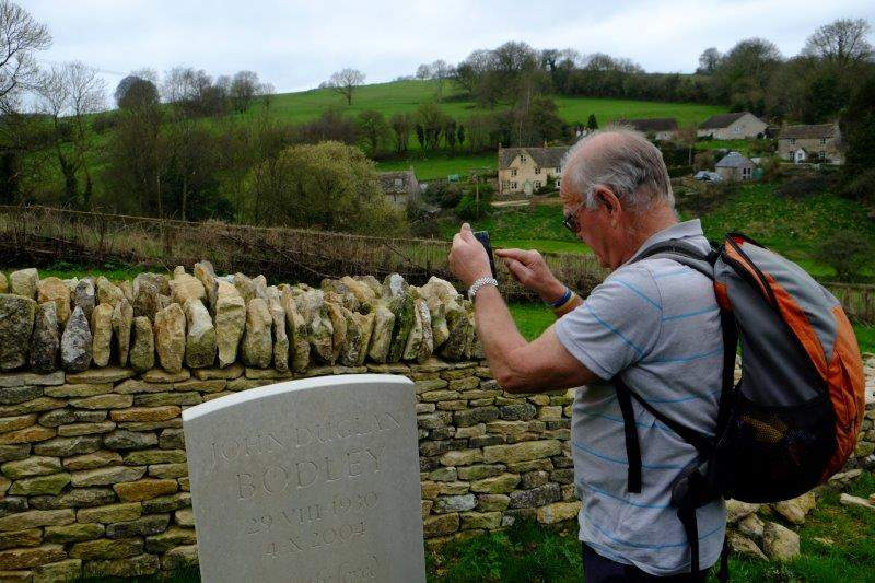 Brian concerned that the grave marker isn't straight and checks it with  an app on his phone