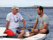 Paul Walker sits with Dr. Michael Domeier and some shark fishing gear.