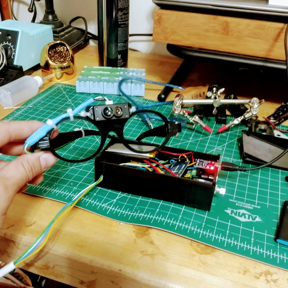 A LiDAR unit mounted to a pair of lasercut glasses with the control box in the background.
