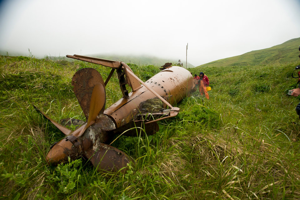 Members of the expedition take time to examine a Japanese mini submarine that remains in the historic sub pens on Kiska Island. Image courtesy of Kiska: Alaska's Underwater Battlefield expedition.