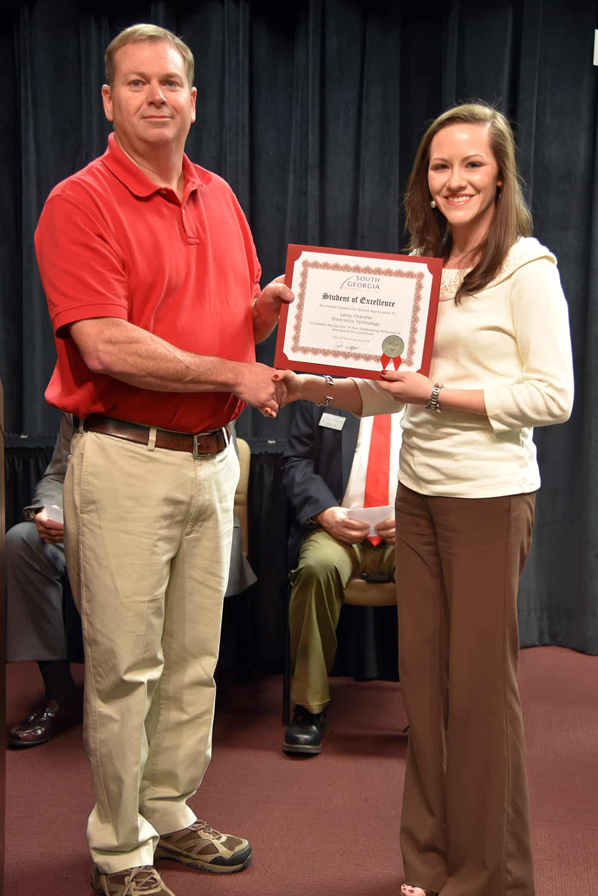 Lacey Chandler accepts her nomination certificate from nominating instructor Mike Collins.