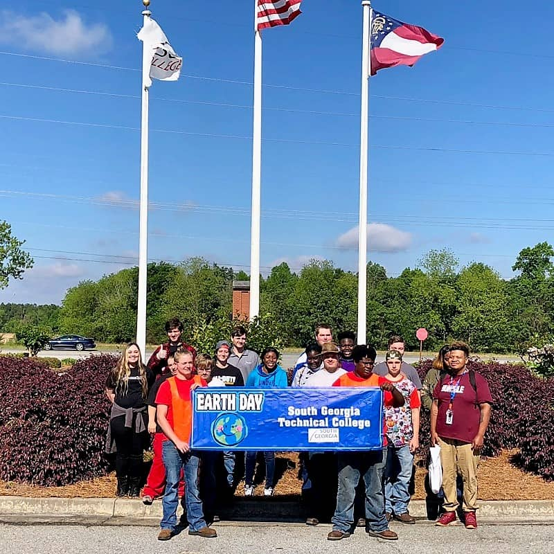 A group of students stand in front of three flag poles.