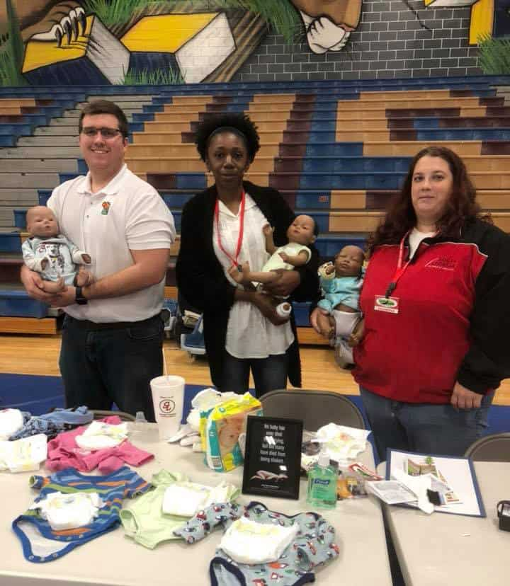 Three people stand in a high school gym behind a table scattered with baby clothes. Each person holds a baby doll.