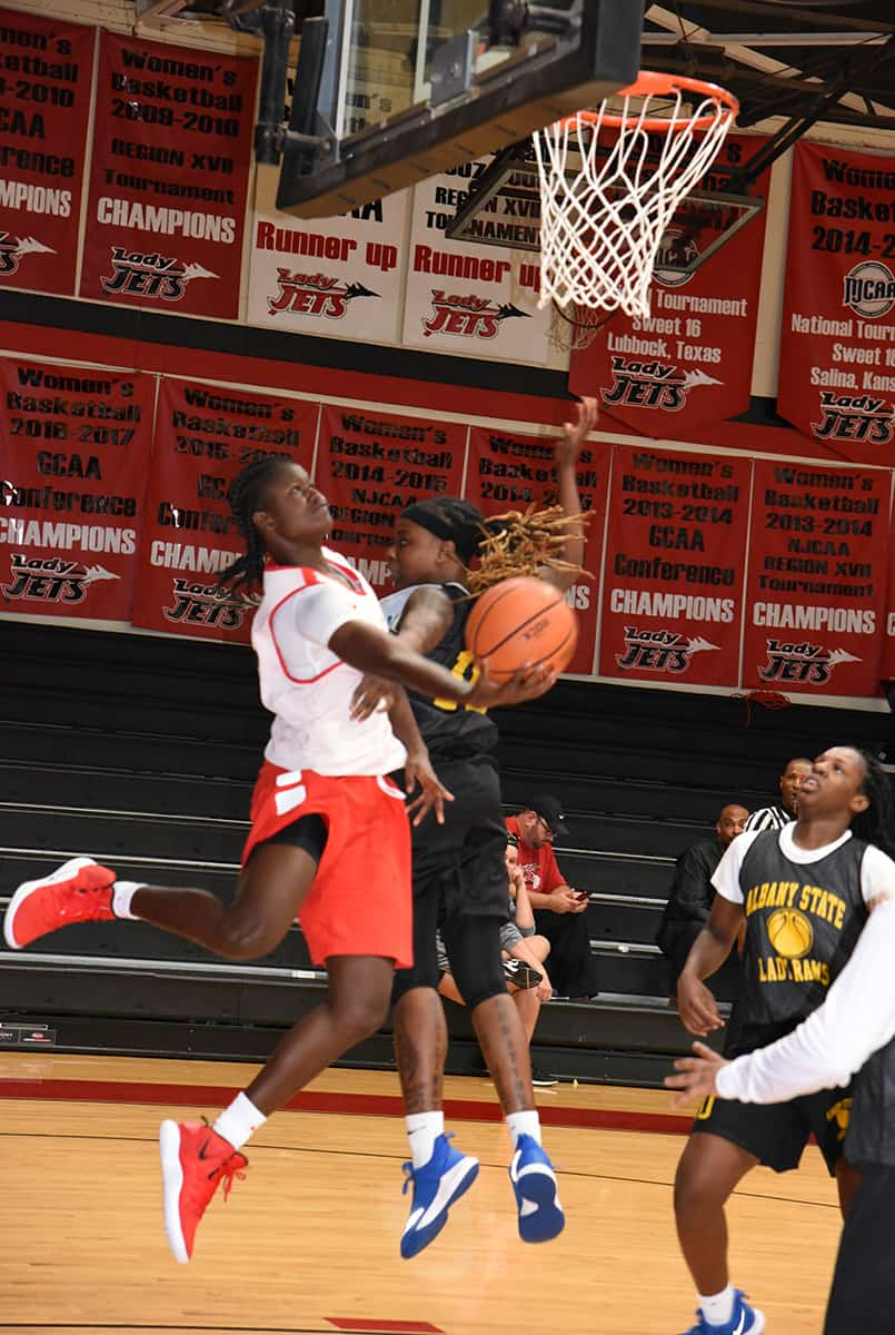 Fatou Pouye, 12, a sophomore from Kaolack, Senegal, came away with 11 points against Albany State.  She is shown driving under the basket for a reverse layup.