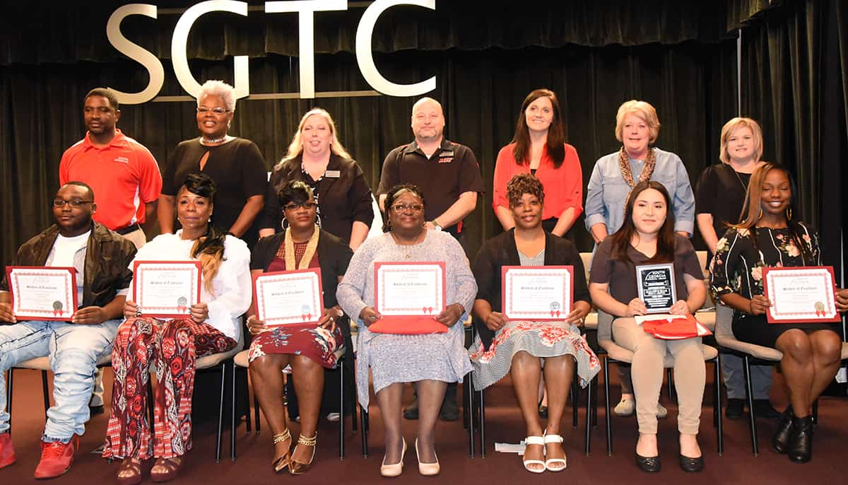 Shown above seated from left to right are Student of Excellence nominees Donterrius Bryant, Cloretha Mitchell, Cynthia Lucas, Gussie Jackson, Cherisse Fletcher, Elizabeth Elias, and Carswella Major. Standing left to right are their instructors,  Xavier Jackson, Dorothea Lusane McKenzie, Teresa McCook, Chef Ricky Watzlowick, Victoria Kelley, Lynn Lightner, and Christine Rundle.