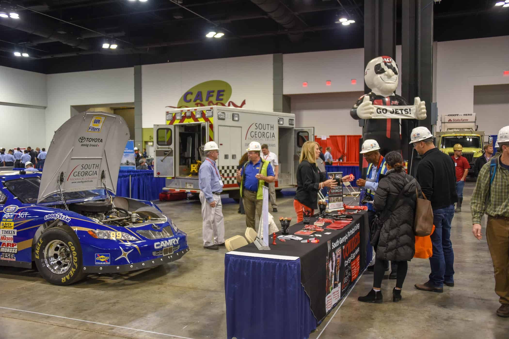 A racecar, ambulance and inflatable mascot occupy a large area within a building.