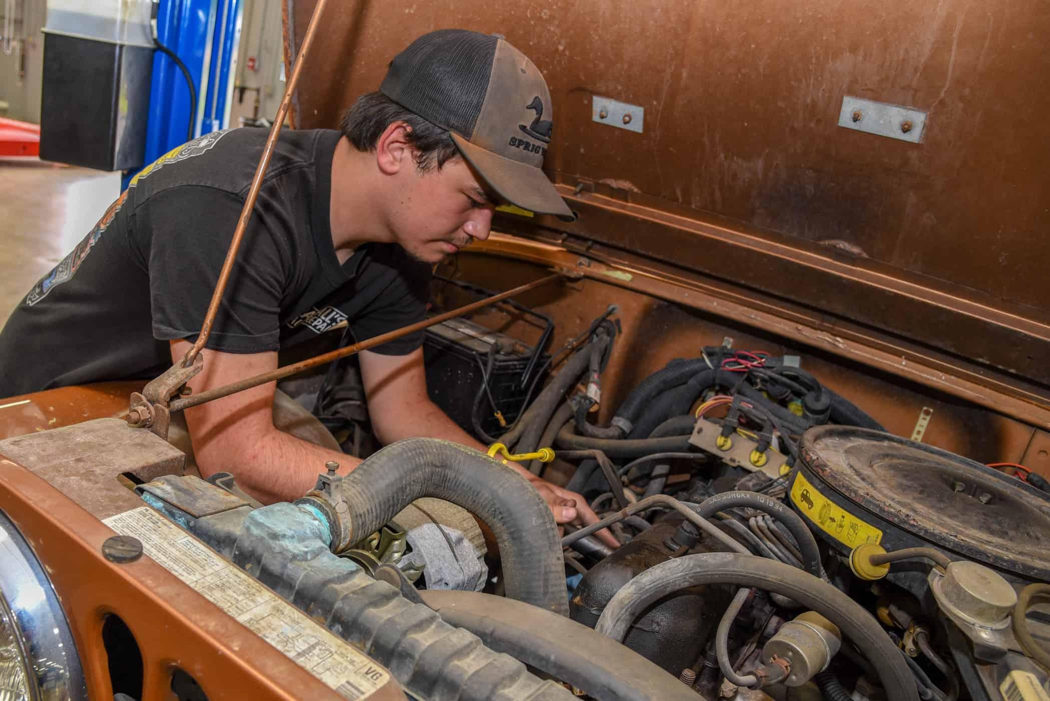 Christopher Waller works under the hood of an burnt orange jeep