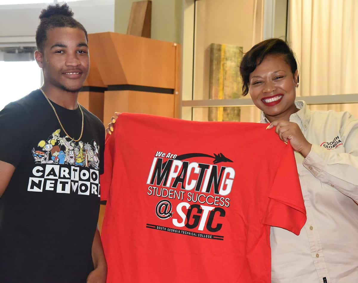 SGTC English Instructor Raven Payne is shown presenting a new Fall Semester student with an Impacting Success t-shirt at the July 17th registration day event.