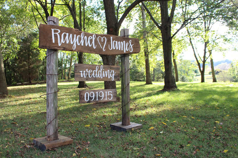 Handmade rustic fence post wedding sign for an outdoor country wedding. Hand painted lettering by South Ranch Creative. Photograph by Summer Kelley Photography.