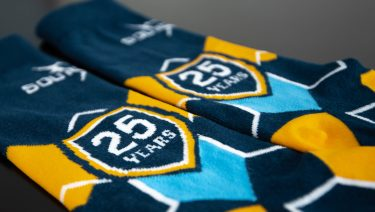 close up photo of customized Southtech dress socks displaying the 25th anniversary logo