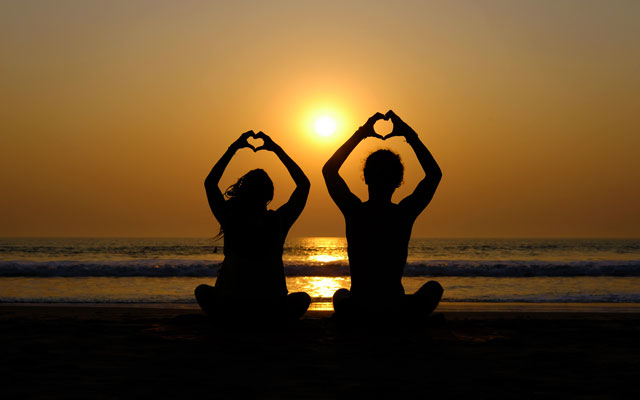Couple's silhouette drawing hearts with their hands on the beach at sunset, Gokarna (Karnataka, India)