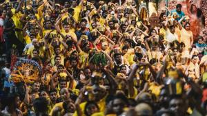 Thousands and hundreds of hindu prayers wearing yellow color shirts waiting in front of the entrance of batu cave temple to worship their god during the night of thaipusam in malaysia