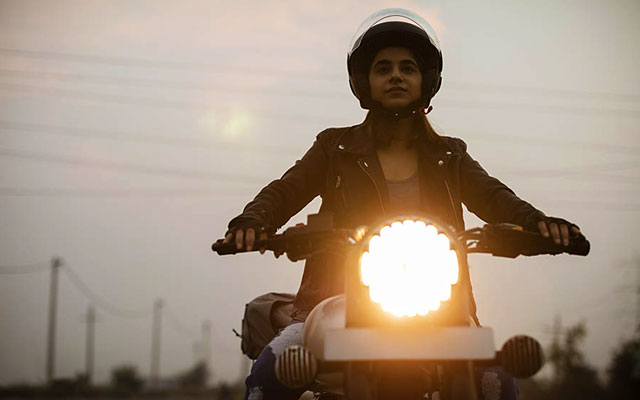 A young Indian solo female traveler riding in a bike