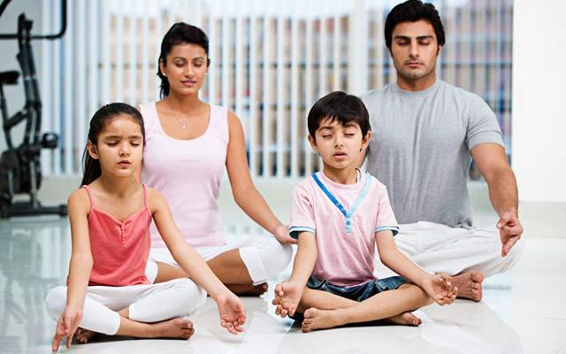 Indian family practicing Yoga & Meditation