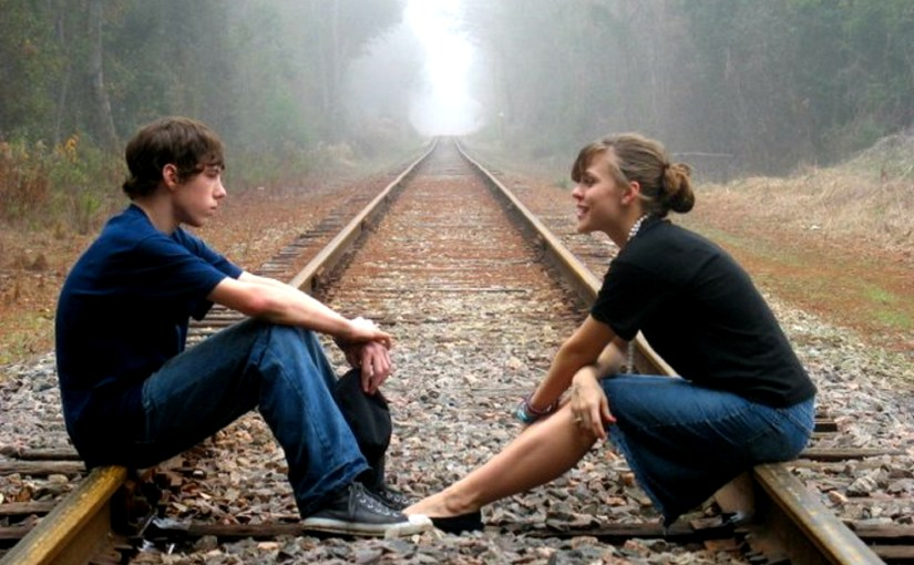 two young people talking and sitting on railroad tracks