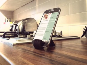 simple-black-metal-tablet-and-ipad-stand-for-cooking_wooden-varnished-countertop_stylish-ipad-stand-for-cooking-under-cabinet-kitchen_white0-ceramic-tiled-backsplash_kitchen-appliances-945x709
