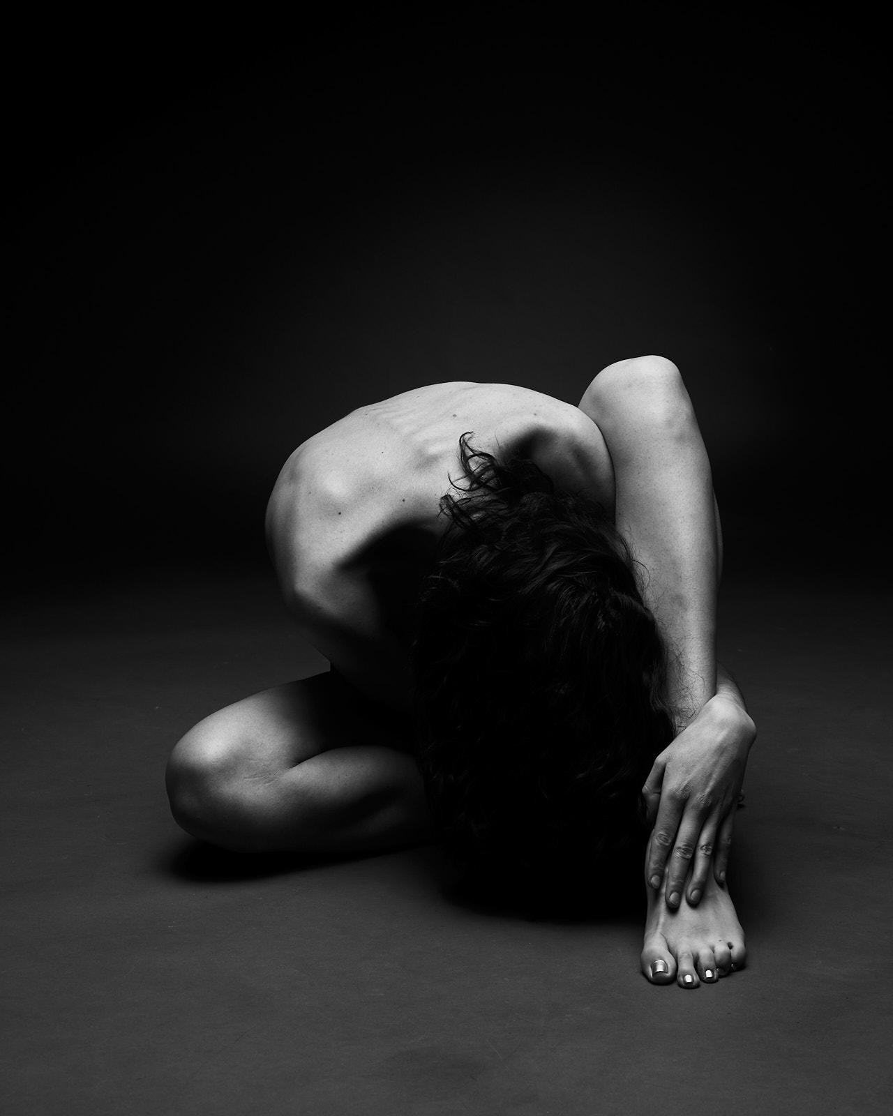 Une femme nue accroupie pied en avant, nu académique, artistique