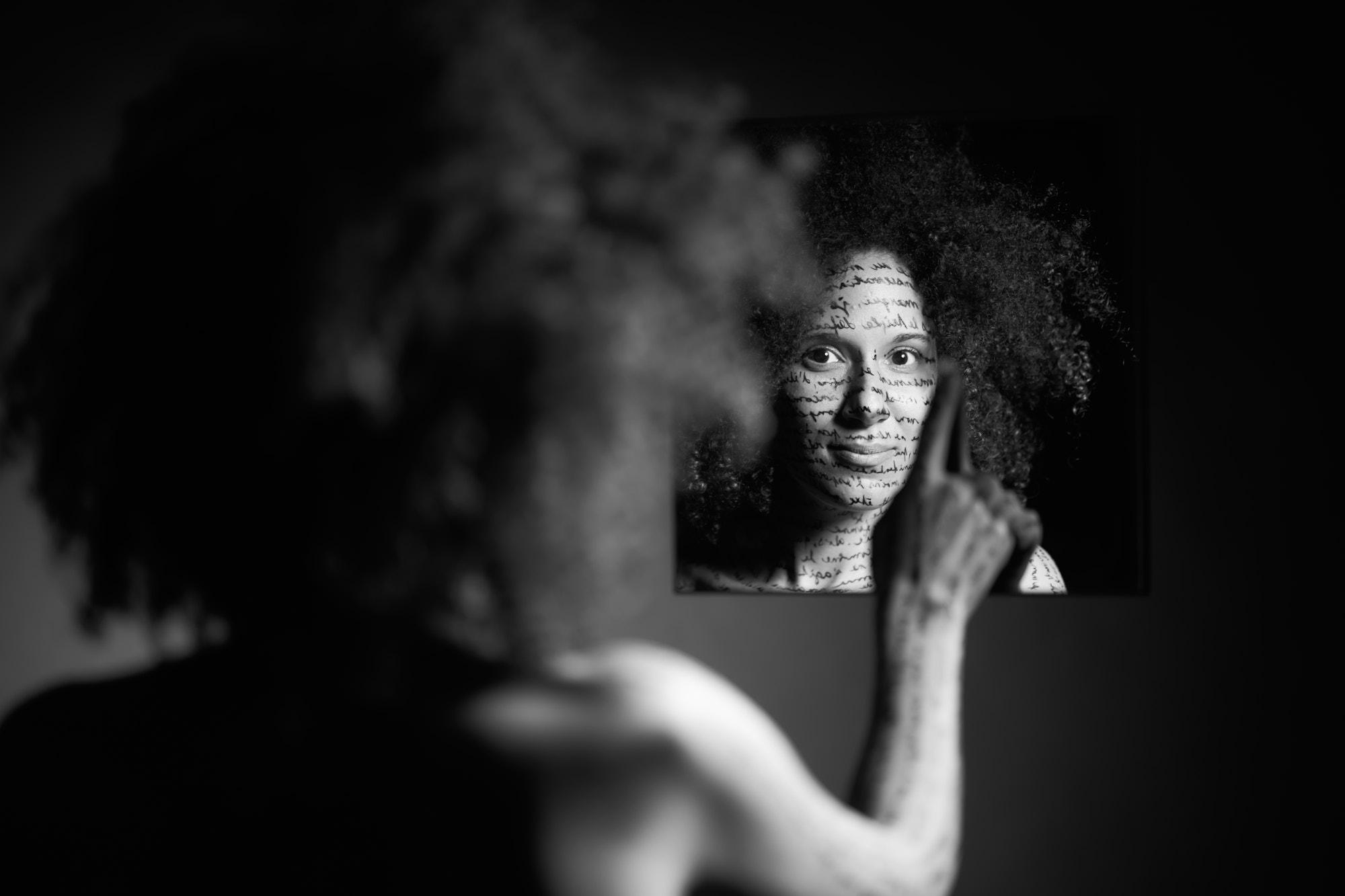 Une femme de dos qui regarde dans un miroir, écriture sur le corps