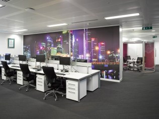 Image of Thomas Cook HQ back-to-back bench desking, featuring monitor arm ergonomics, slat wall railing. Also shows digital wallpaper graphics and meeting pod