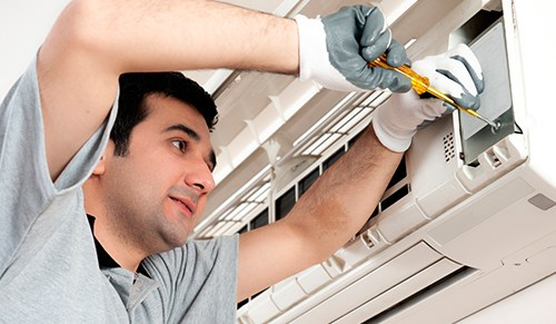 image of an office maintenance engineer fixing an air conditioning unit