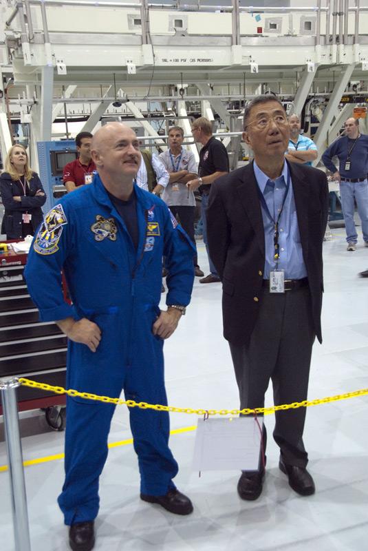 Mark Kelly e Sam Ting observam o AMS-02 em uma estante no KSC (Foto: Cory Houston / NASA)