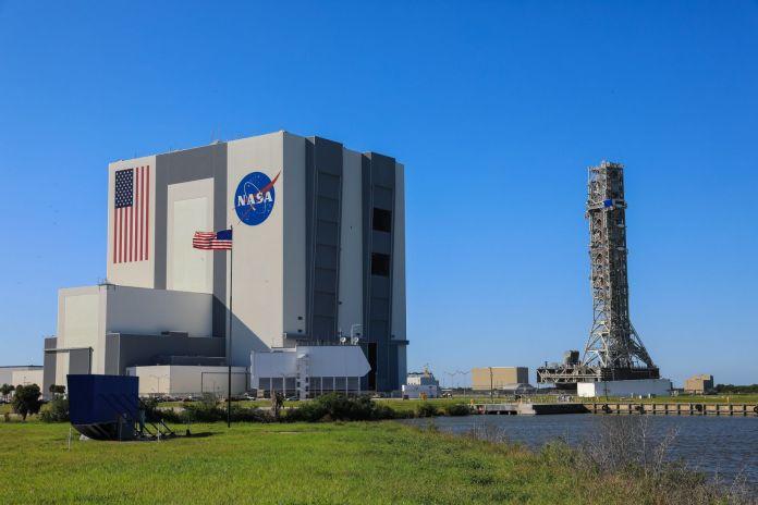 बूस्टर स्टैकिंग शुरू होने से पहले वाहन असेंबली बिल्डिंग के बाहर देखे गए नासा मोबाइल लांचर।  साभार: NASA