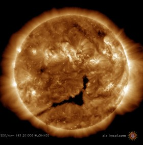 A coronal hole, seen as the large dark region in the center of this image, is spewing solar wind in the direction of Earth (Credits: NASA SDO/AIA).