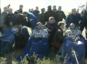 Expedition 35 crew, seated, catch their breath after landing. From left: Chris Hadfield, Roman Romanenko, and Tom Marshburn (Credits: Roscosmos/NASA).