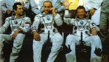 Jean-Loup Chretien (right) waves to well-wishers in the aftermath of his safe landing. Commander Vladimir Dzhanibekov (center) reports by telephone the flight's successful completion, whilst Aleksandr Ivanchenkov looks on (Credits: SpaceFacts.de/Joachim Becker).