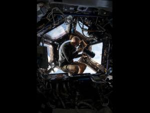 Chris Cassidy conducts Earth observations and photography in the space station's multi-windowed cupola (Credits: NASA).